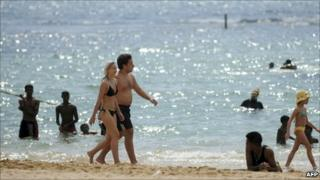 Tourists walk on a beach in Sri Lanka's southern coastal city of Hikkaduwa, 30 January 2011