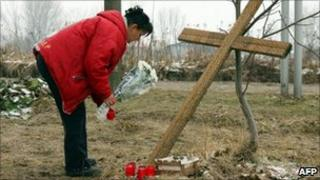 A woman leaves flowers at the scene of the crash near Hordorf (31 Jan 2011)
