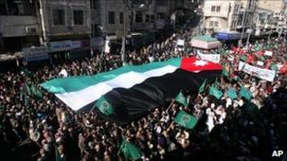 Protesters carry a national flag in Amman, Jordan (21 Jan 2011)