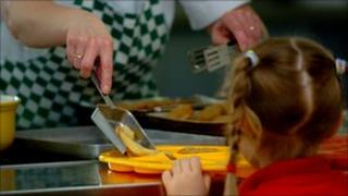 Pupil being served school meal