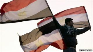 A protester in Tahrir Square holds Egyptian flags - 1 February 2011