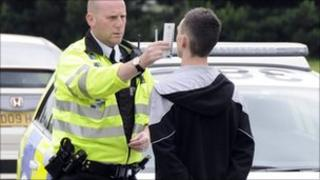 Police officer checking youth's pupil dilation