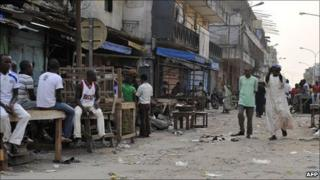 People walk by closed shops in Abidjan, Ivory Coast, on 18 January 2011
