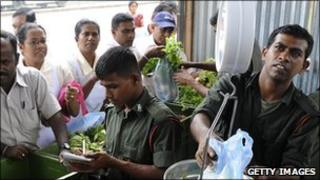 Soldiers sell vegetables from a stall in Colombo