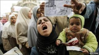 A protester carries her child as she chants anti-government slogans during demonstrations in Alexandria, Egypt