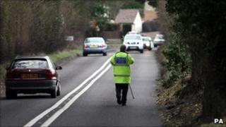 Police attend the site of a fatality where a man was killed by a tree falling in high winds