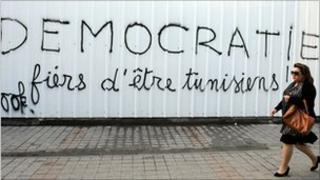 "Woman walks past graffiti reading ""Democracy, Proud to be Tunisian"", Tunis."