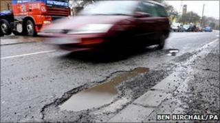 Car drives past pothole