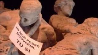 "A banner on a statue in Rome which reads: ""I can't go anywhere, you can"""
