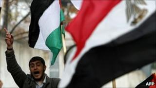 Palestinian protester holding an Egyptian flag outside the Egyptian diplomatic mission in Gaza City