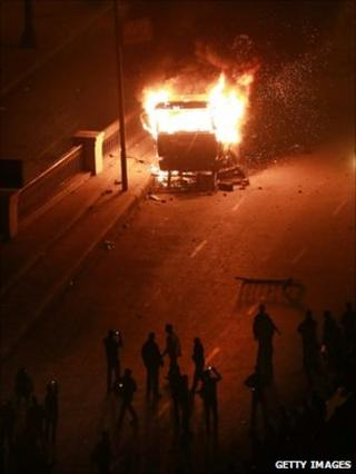 Protesters use their mobile phones to photograph a burning police vehicle during clashes in Cairo on 28 January 2011