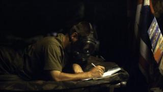 A soldier wearing a gas masks writes a letter during the Gulf War, 1991