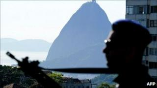 The silhouette of a Brazilian military policeman in front of Rio de Janeiro's landmark Sugar Loaf hill