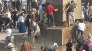 People sweeping the street and removing graffiti in Cairo's Tahrir Square