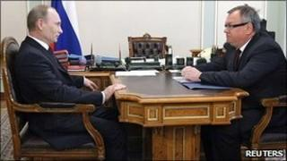 Russian Prime Minister Vladimir Putin listens to VTB head Andrei Kostin