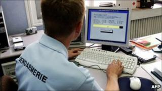French policeman examining a computer hard drive - file pic