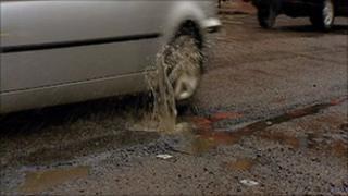 Car driving over potholes