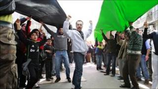 Supporters of the opposition parties carry a giant national flag during Amman protests, 18/02