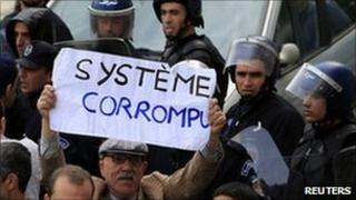 "An anti-government protesters holds a sign on which reads ""Corrupted system"" during a demonstration in Algiers on 19 February 2011."