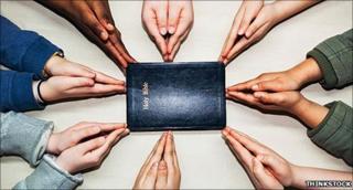 Hands round a bible