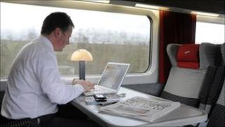 man working at computer on train