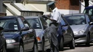 Parked cars and a traffic warden