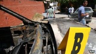 People stand near a burnt vehicle in Acapulco, 20 February