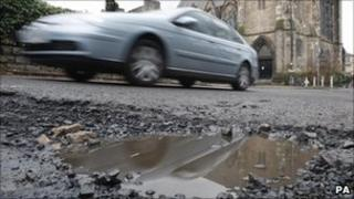 Car driving over potholes