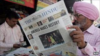 Indian Sikh man browses newspaper in shop