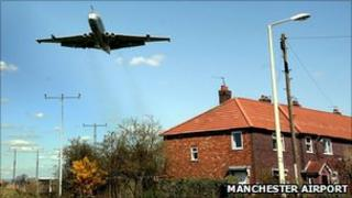 A plane flies over a house near Manchester Airport