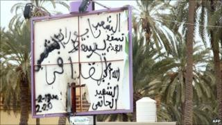 Anti-Gaddafi graffiti is sprayed on a billboard that used to carry portraits of the Libyan leader in front of Tripoli's Friday market police station which was allegedly attacked by demonstrators on 21 February 2001