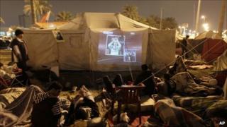 Bahraini demonstrators watch TV in Pearl Square, 17 Feb