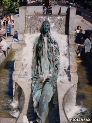 Statue of an elongated woman lying in an artificial waterfall display