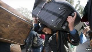 An Egyptian flees Libya at the Ras Jdir border post in Tunisia
