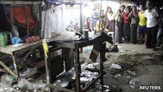 Bystanders look on after a blast in Rangoon, Burma, 27 February 2011