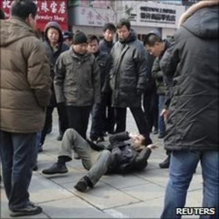Unidentified men surround a foreign journalist after they pushed him to the ground in Wangfujing, Beijing, 27 February