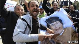 Protesters deface a poster of Col Gaddafi