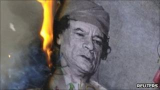 A man burns a picture of Libyan leader Muammar Gaddafi during a demonstration near the Libyan consulate in Paris on 25 February 2011