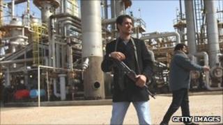 A militiaman stands guard with a gun at an oil refinery in Brega, Libya