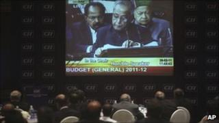Businessmen watch Pranab Mukherjee present the budget
