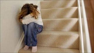 Child on stairs hiding head in hands