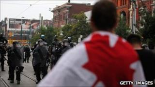A protester faces the police in Toronto