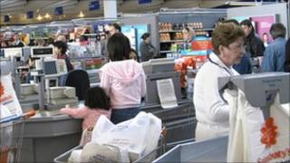 Shoppers check out at a Sainsbury's store, with beer for sale nearby