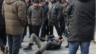 A journalist lies on the ground surrounded by the men who pushed him, in Beijing on 27 February 2011
