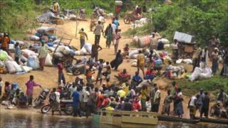 Ivorian fleeing into Liberia across a river