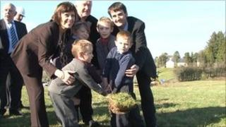 Teachers and children digging with spade