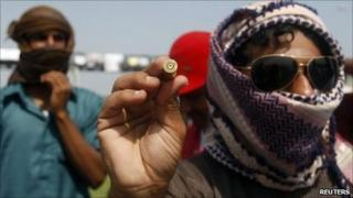 A protester holds up a spent bullet casing, which he says is from anti-riot police firing their weapons into the air in Sohar. Photo: 1 March 2011