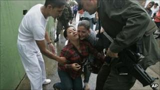 Relatives of dead policemen being helped by a paramedic and a police officer in Caloto, Colombia
