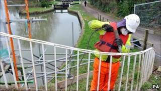 Chris Eade from Bristol removes paint from the Bath Top Lock footbridge on the Kennet and Avon Canal in Bath