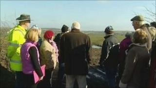 Villagers look at the site of the proposed slurry lagoon